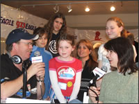 Morning Show Personalities Jimmy Ray Dunn (l) and Jennifer Lewis (right) interviewing kids who raised $505 with their bake sale.